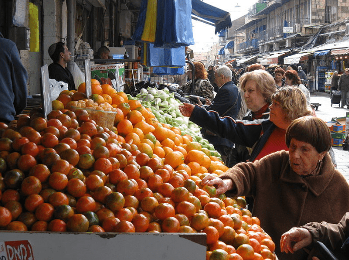 People buying fruit from a fresh produce market
